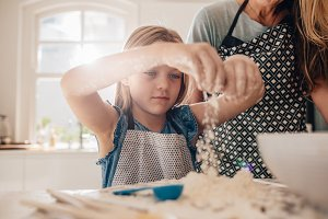 Beautiful little girl learns to cook