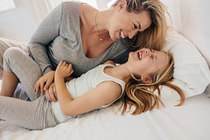 Mother on bed playing with daughter