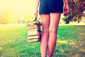 Girl holding a stack of books.