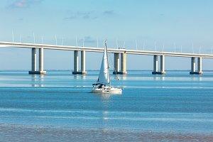 A Sailboat near a Long Bridge