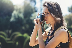 Girl photographs on a vintage camera