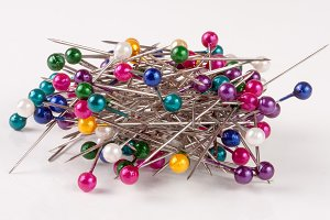 pile of  multi-colored sewing pins on a white background