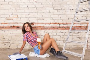 woman paints white brick wall with paint brush