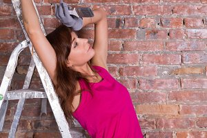 woman painter on a ladder near brick wall