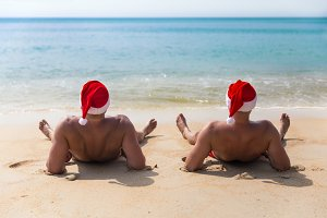 Man in Christmas red hat on tropic sea beach