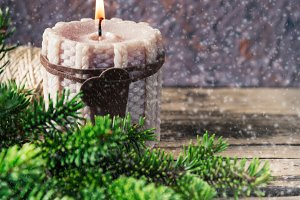 knitted candle pine and snow on wooden background
