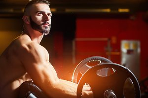 Young muscular man training biceps with barbells in gym