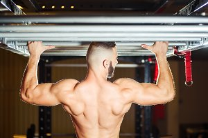 Athlete muscular fit man pulling up on horizontal bar in a gym
