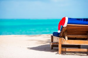 Santa Claus Hat on beach lounger with turquoise sea water and white sand. Christmas vacation concept