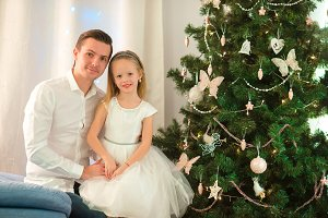 Father hugs daughter near the Christmas tree on xmas eve