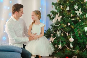 Father with little cute girl near the Christmas tree on xmas eve