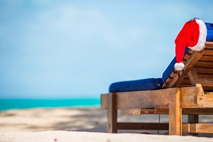 Santa Hat on beach lounger. Christmas vacation concept