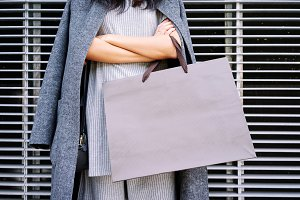 Female holding a blank paper bag