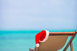 Christmas on the beach - chair with Santa hats at sea. Christmas vacation concept