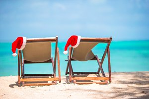 Christmas on the beach -chair lounges with Santa hats at sea. Christmas vacation concept