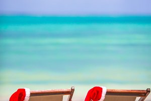 Sun loungers with Santa hat at tropical beach with white sand and turquoise water