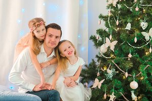 Happy dada with kids near the Christmas tree on xmas eve