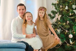Happy father with kids near the Christmas tree on xmas eve