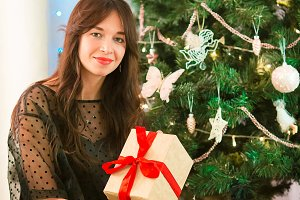 Happy young woman holding christmas present box on Christmas eve