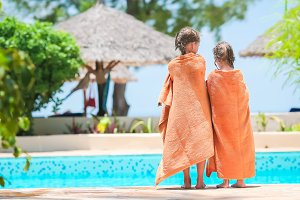Adorable little girls wrapped in towel on the edge of pool