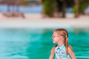 Little happy adorable girl on the edge of outdoor pool