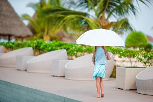 Little girl with an umbrella in hands walking near outdoor pool