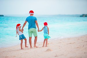 Little girls and young dad in Santa Hats enjoy Christmas vacation