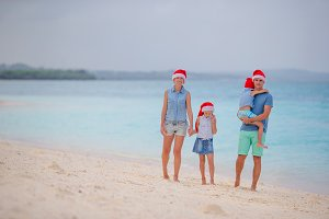 Happy family in red Santa hats on tropical beach celebrating Christmas