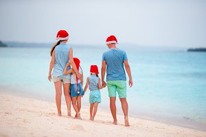 Happy beautiful family in red Santa hats on tropical beach celebrating Christmas