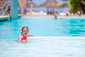 Little happy adorable girl swimming in outdoor pool