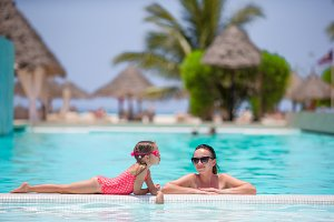 Mother and kid enjoying summer vacation in luxury swimming pool