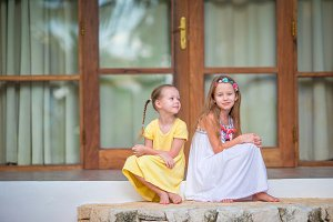 Adorable little girls on terrace during summer vacation