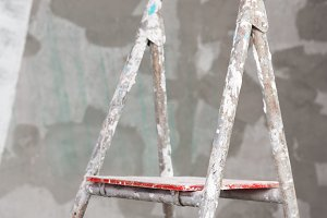 Old painted and stucco ladder on concrete wall