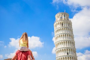 Family of dad and kid background the Learning Tower in Pisa. Pisa - travel to famous places in Europe.