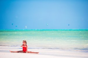 Sporty adorable little girl on white beach having fun