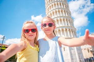 Little tourists girls taking selfie background the Leaning Tower in Pisa, Italy. Photo about european vacation