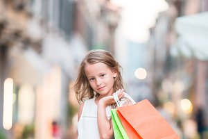 Adorable little girl walking with shopping bags outdoors in Europe. Fashion toddler kid in Italian city with her shopping