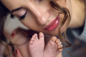 young mother kissing the heels