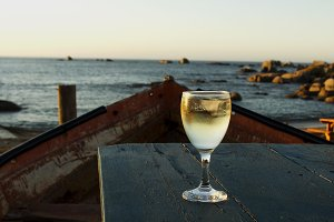 glass of white wine on the old boat at sunset, selective focus