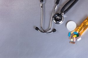 Stethoscope and Medicine on table