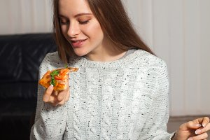 Woman is holding a slice