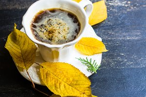 Cup of coffee with yellow leaves
