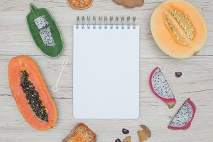 Notebook with exotic fruits on wooden background.