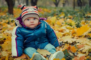 Baby is sitting in fallen leaves