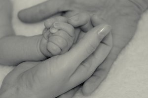 Baby's hand in the hands of parents