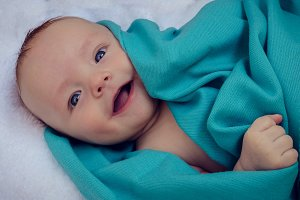 Smiling baby covered in blue blanket