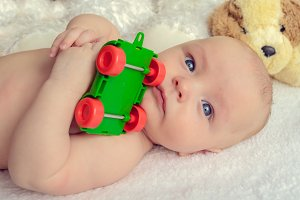 Serious baby with a toy car