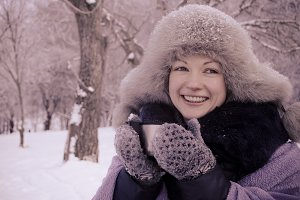 Smiling woman holding a travel mug in winter