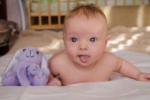 Naked baby showing tongue