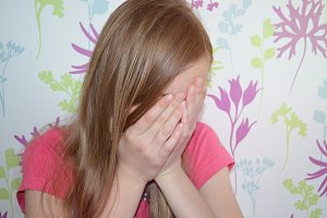 Teen girl is covering her face by hands